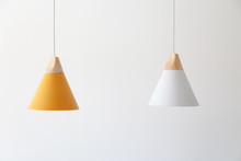 White And Yellow Lamps With Light Wooden Parts Are Hanging On The Cables