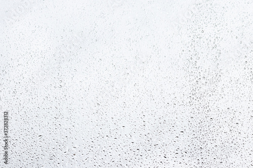 Leinwand Poster Rain drops on window glasses surface with gray sky background