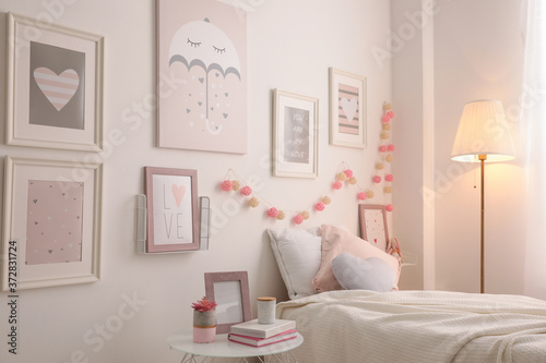 Foto Stylish child's room interior with beautiful pictures and comfortable bed
