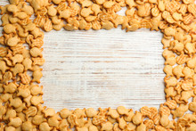 Frame Of Delicious Goldfish Crackers On White Wooden Table, Flat Lay. Space For Text