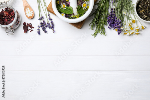 Foto Flat lay composition with healing herbs on white wooden table