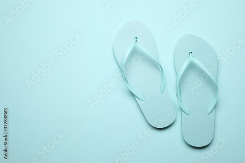 Obraz na plátně Pair of stylish flip flops on light blue background, top view with space for text