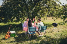 Full Length Photo Of Four People Students Fellows Gathering Table Feast Celebrate Girls Guys Summer Birthday Clink Cheers Chill Beer Bottle Under Green Tree Garden Outside
