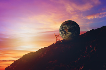 Business Challenge and Success Concept : Wooden figure pushing blue earth uphill to top of mountain with sunset and beautiful sky in background. (Elements of this image furnished by NASA.)