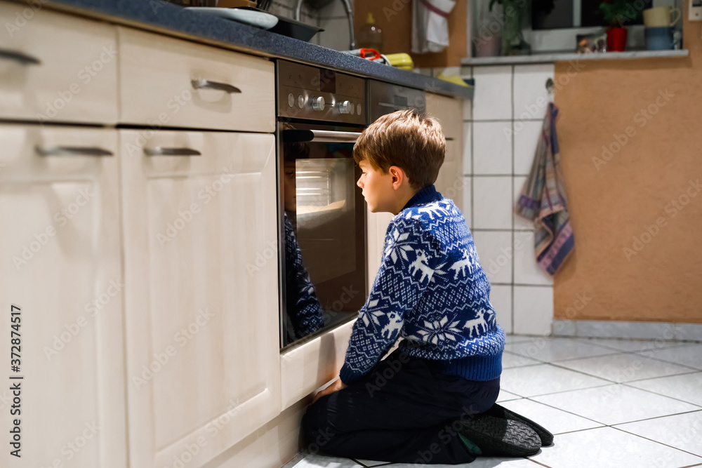 Fototapeta Cute funny blond kid boy baking muffins in domestic kitchen. Child having fun with helping, sitting near ofen and waiting for cupcakes