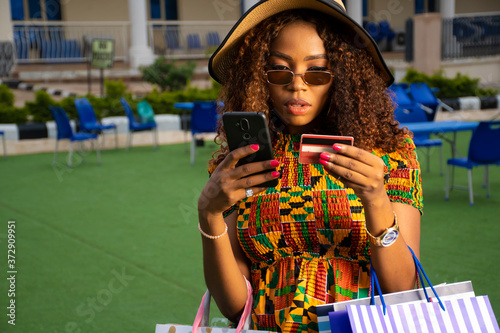 Obraz young african woman using her phone and credit card outdoor - fototapety do salonu