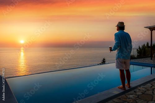 Fototapeta Ein attraktiver Mann mit Hut steht am Pool und genießt den Sommer Sonnenuntergan