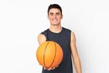 Handsome young basketball player man over isolated wall playing basketball