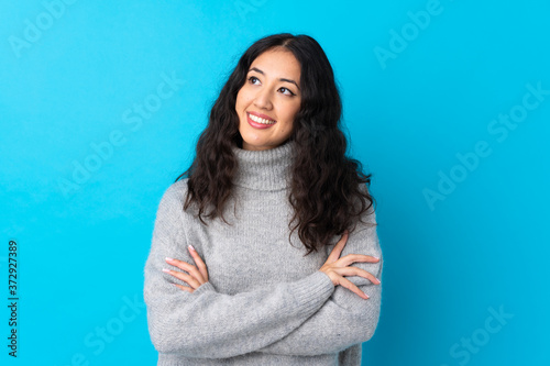 Fotografie, Obraz Spanish Chinese woman over isolated blue background looking up while smiling