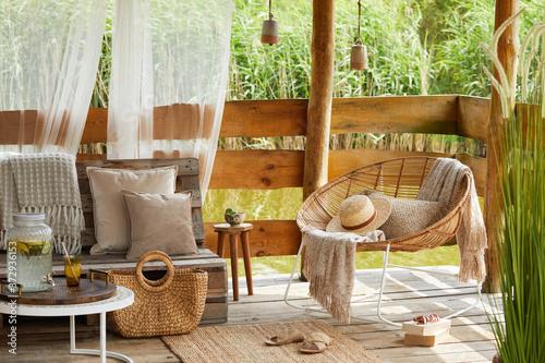 Carta da parati Interior design of  summer gazebo by the lake with stylish rattan armchair, coffee table, sofa, pillows, plaid and elegant accessories in modern decor