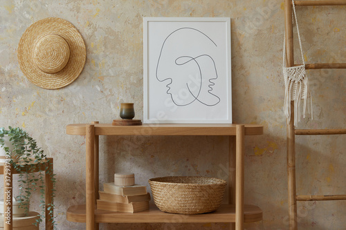 Fototapeta Bohemian interior of living room with mock up poster frame, elegant rattan accessories, dried flowers in vase, wooden console and hanging hut in stylish home decor