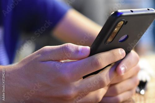 Photo Smartphone consultado relajadamente por un joven en luminoso entorno laboral tec