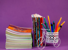 School And Office Supplies, General And Simple Notebooks With Colored Pens And Pencils In A Stand On A Purple Background. Color Trend.