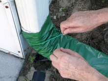 A Man Is Installing An Automatic Recoiling Extender Over The Gutter Downspout That Rolls Out When It's Raining And Retracts When It's Dry To Prevent Foundation Damage From Water.