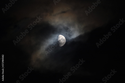 Fotografiet Mesmerizing view of a moon with clouds at night