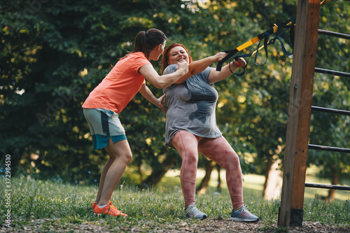 Foto An obese woman together with her trainer during weight loss training, does arm a