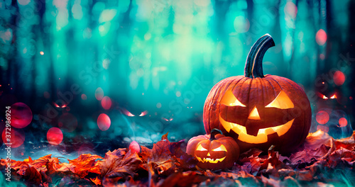 Photo Jack O' Lanterns On Red Leaves In Spooky Forest With Defocused Ghosts