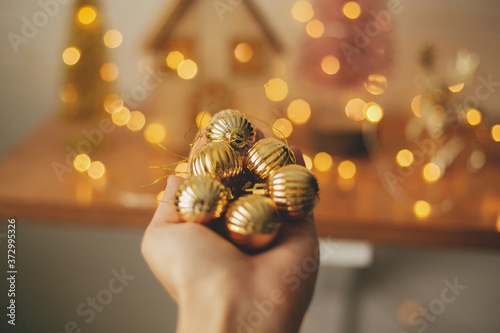 Hand holding modern gold baubles on background blurred illumination lights Fototapete