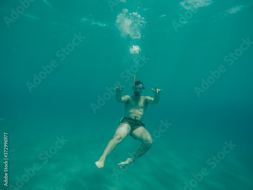 Young boy diving under the sea. Fototapet