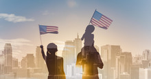 Patriotic Man, Woman, And Child Waving American Flags In The Air On City Sunrise Background