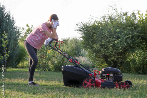 Obraz Tired woman making a short break while cutting grass with a lawn mower. Outdoor household chores concept. - fototapety do salonu