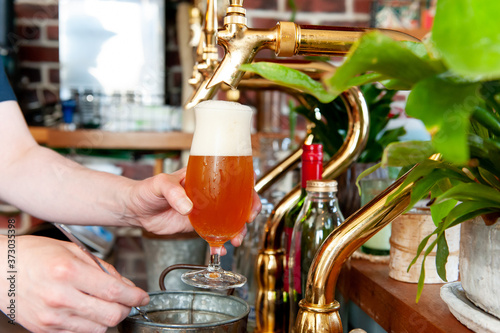 ビールサーバー(ビールタップ)でグラスにビールを注ぐシーン   Fototapet