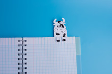 Open Copybook With Paper Cow Bookmarks , Soft Focus, Top View, Blue Background