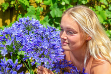 Young Blonde Woman Smelling Blue Flowers