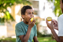 Two Boys Eat A Lemon On A Sunny Day, One Of Them With His Mouth Wide Open