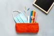 canvas print picture - Orange Federmappe mit einem blauen Mundschutz, Farbstifte, ein rosa Herz Lutscher und eine Schultafel. Grauer Hintergrund, Flat lay, neue Normalität.