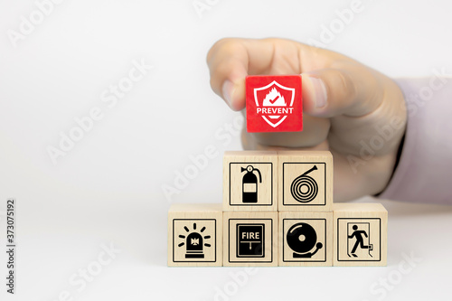 Valokuvatapetti Close-up hand choose fire prevent icon on cube wooden toy blocks stacked with fire prevention icon for safety emergency concepts