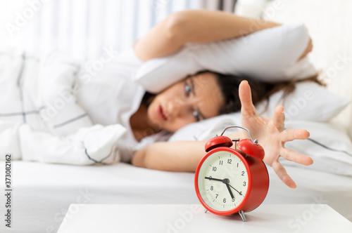 Wake up of an asleep woman stopping alarm clock Canvas Print