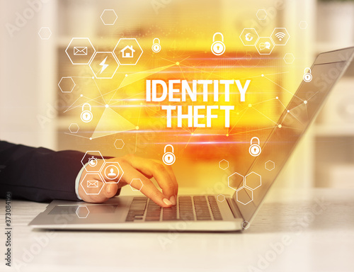 Fotografie, Obraz IDENTITY THEFT inscription on laptop, internet security and data protection conc
