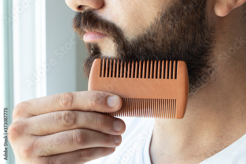 Foto Bearded man comb his beard