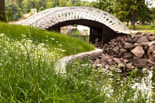 White Arched Bridge Overhanging The Water Surrounded By Green Grass And Granite Stones