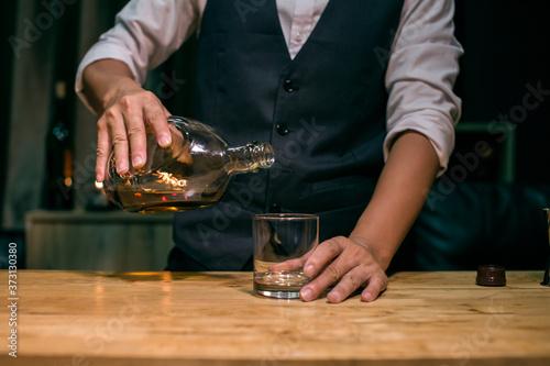 Barman pouring whiskey whiskey glass beautiful night Fototapet