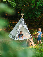 Two Young Boys Playing In A Backyard Teepee Campsite Under The Summer Sunset