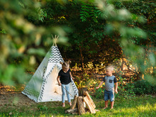 Two Young Kids Roast Marshmallows In The Backyard Next To A Play Teepee