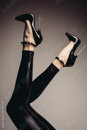 Fotografering Slender female legs in spandex catsuit and a fetish shoe with extremely high heels