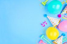 Birthday Party Side Border On A Blue Background. Above View With Confetti, Balloons, Party Hats And Streamers. Copy Space.