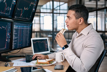 Stock Traiding. Trader Sitting At Office In Front Of Monitors With Data Using Trading Bot Make Trades Cryptocurrency Exchange While Having Break Eating Sandwich And Drinking Coffee