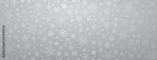 Fototapeta Christmas background of various complex big and small snowflakes, in gray colors
