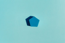 Blue Pentagon Dropping Shadow On A Light Blue Background With A 3d Render Feel Optical Illusion