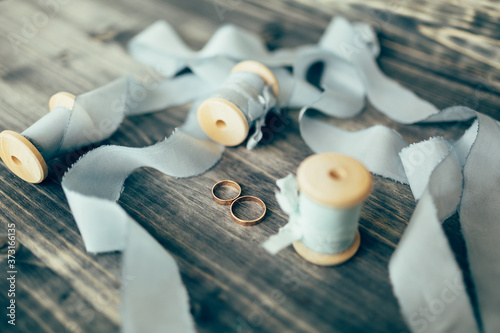 Fényképezés Gold wedding rings on a wooden surface with spools with gray silk ribbons