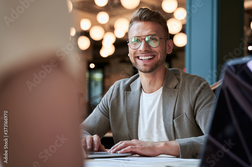 Photo Enthusiastic smiling young businessman at his workplace