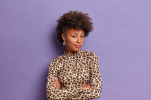 Studio Shot Of Pleasant Looking Woman With Curly Hair, Poses In Confident Pose, Keeps Arms Folded, Looks Seriously At Camera, Has Dark Skin, Isolated On Purple Background. Fasionable Lady Indoor