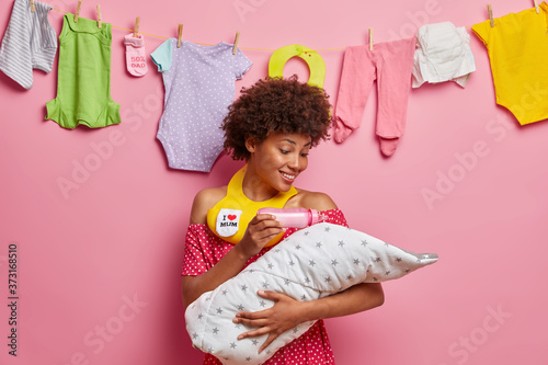 Photo Affectionate cheerful mother feeds newborn baby from bottle, has happy expressio