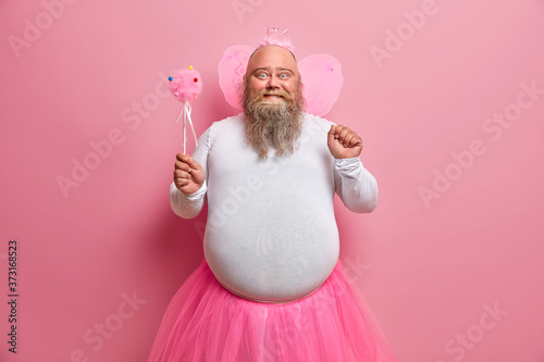 Slika na platnu Positive plump man has fun on theme birthday party, feels like fairy who makes dreams come true, chills with children, has thick beard and fat belly, poses with magic wand and wings on back