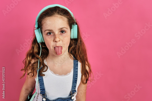Little girl posing with headphones with her tongue out on a pink background Fototapete