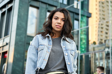 Confident Beautiful Curly Young Hipster African American Woman Wearing Denim Jacket Looking At Camera Standing On Urban City Street. Serious Pretty Black Mixed Race Girl Posing For Portrait Outdoors.